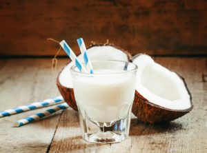 Coconut milk in a glass with striped straw and coconut halves, selective focus