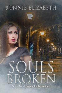 Book cover for Souls Broken a girl looking over her shoulder at a lighted path at night